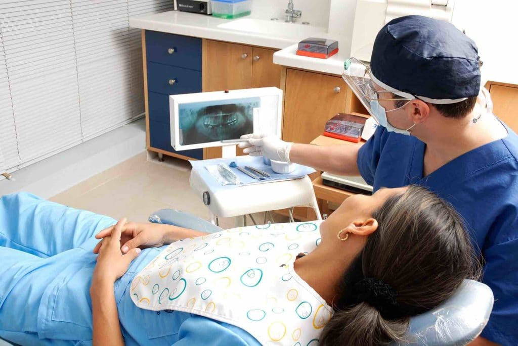Dentist showing teeth alignment results to patient