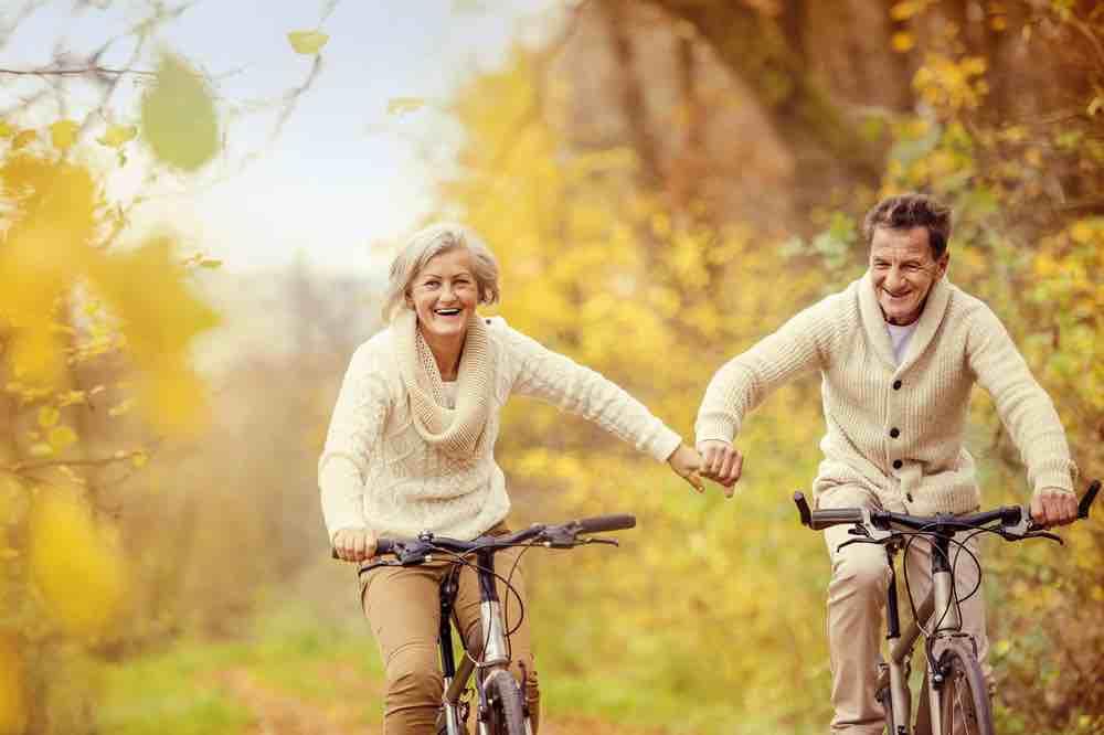 Older couple biking outside