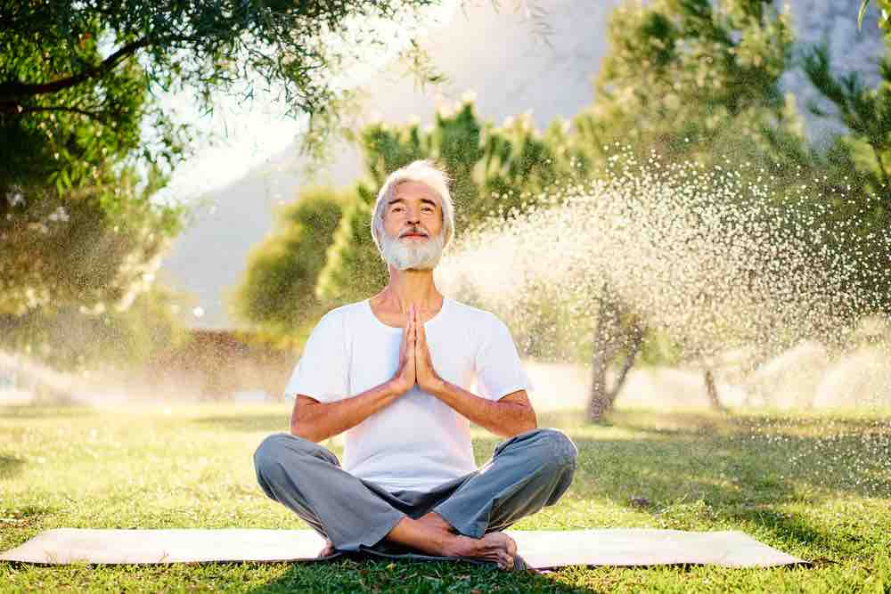 Yoga at park. Senior bearded man in lotus pose sitting on green grass. Concept of pray and meditation.