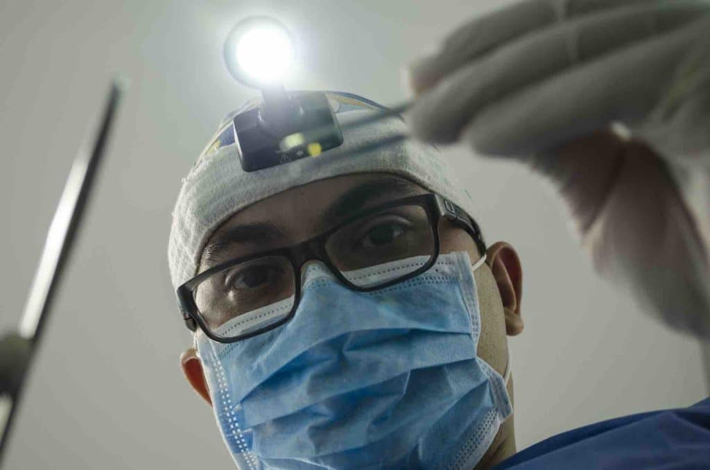Thai dentist performing an operation