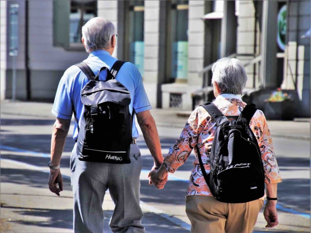 Two healthy seniors holding hands