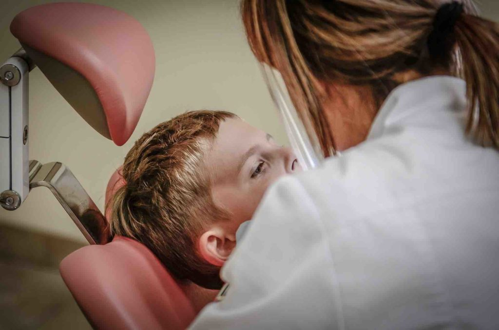 Child getting braces installed by an orthodontist