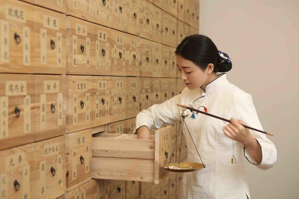 Traditional Chinese medicine doctor weighing herbs