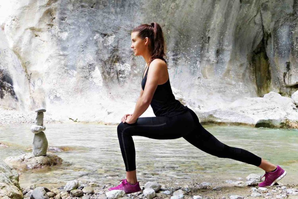 Healthy woman exercising by river