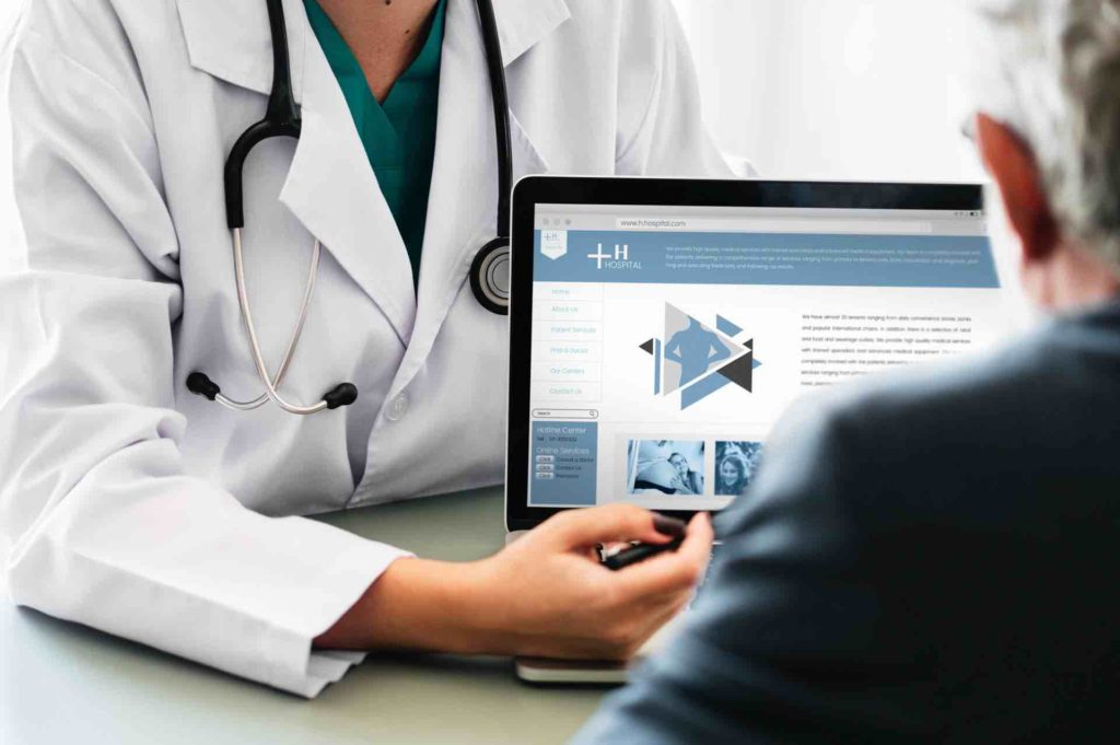 Healthcare professional showing medical software to patient