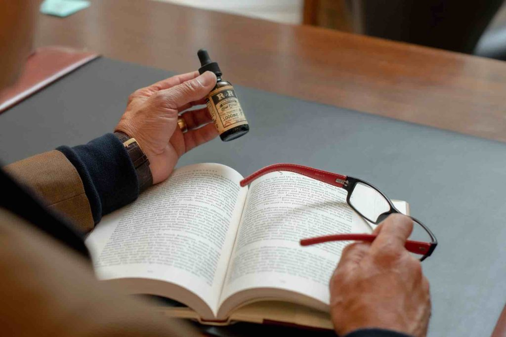 Man with glasses reading and ingesting CBD oil