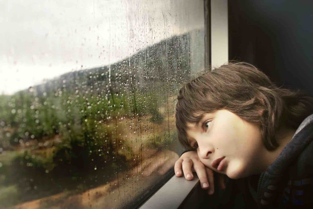 Depressed child looking out the window