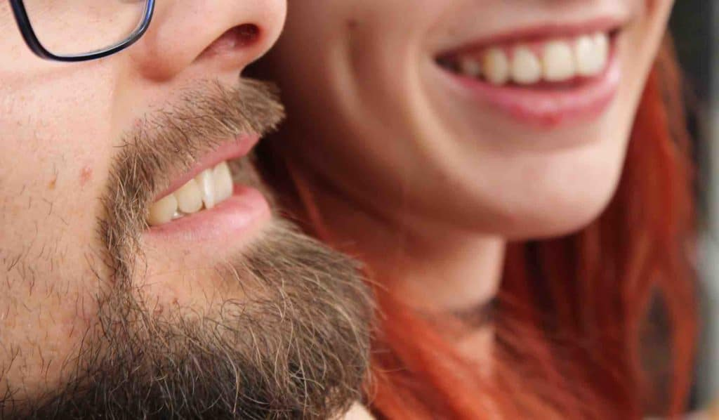 Two people smiling with healthy teeth